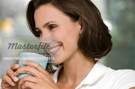 Smiling woman holding cup of coffee Stock Photo - Rights-Managed, Image code: 853-05523410