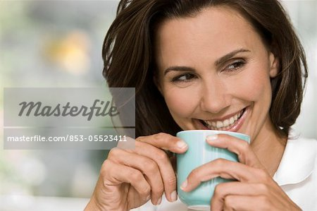 Smiling woman holding cup of coffee Stock Photo - Rights-Managed, Image code: 853-05523411