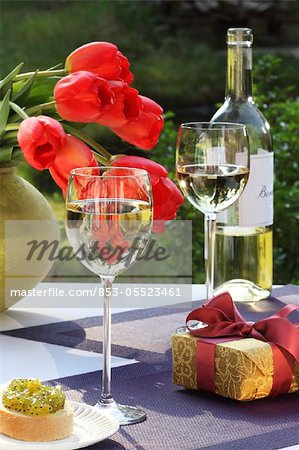 White wine, gift and bunch of tulips on garden table Stock Photo - Rights-Managed, Image code: 853-05523461