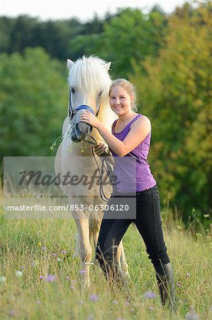 Smiling girl with horse on meadow Stock Photo - Rights-Managed, Image code: 853-06306120