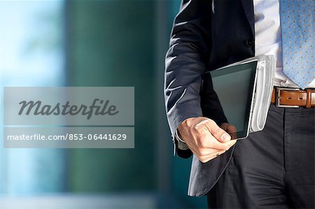 Businessman carrying tablet PC and newspaper under his arm Stock Photo - Rights-Managed, Image code: 853-06441629