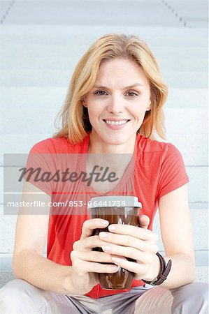 Blond woman with coffee to go on stairs Stock Photo - Rights-Managed, Image code: 853-06441738