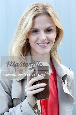 Smiling blond woman holding coffee to go Stock Photo - Rights-Managed, Image code: 853-06441753