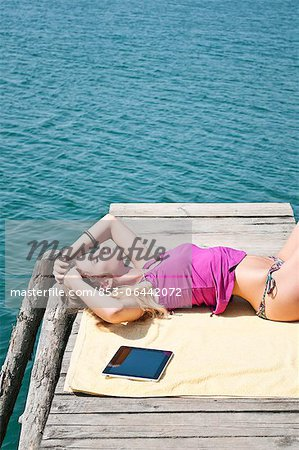 Blond young woman lying on jetty at a lake Stock Photo - Rights-Managed, Image code: 853-06442072