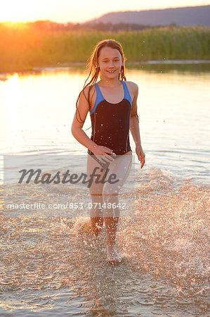 Girl running in the shallow water of a lake Stock Photo - Rights-Managed, Image code: 853-07148642
