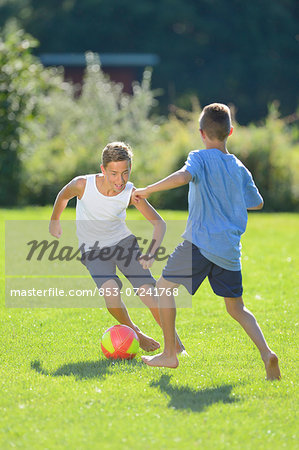 Two teenage boys playing football on a meadow, Upper Palatinate, Bavaria, Germany, Europe Stock Photo - Rights-Managed, Image code: 853-07241768