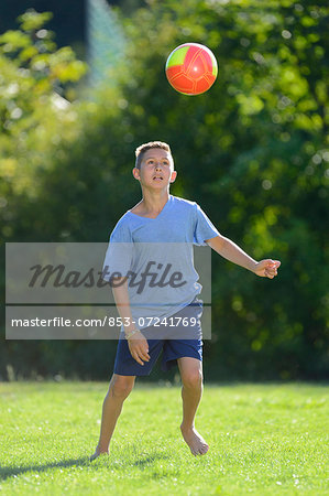 Teenage boy playing football on meadow, Upper Palatinate, Bavaria, Germany, Europe Stock Photo - Rights-Managed, Image code: 853-07241769