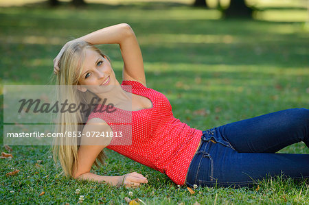 Young blond woman lying in a park Stock Photo - Rights-Managed, Image code: 853-07241813