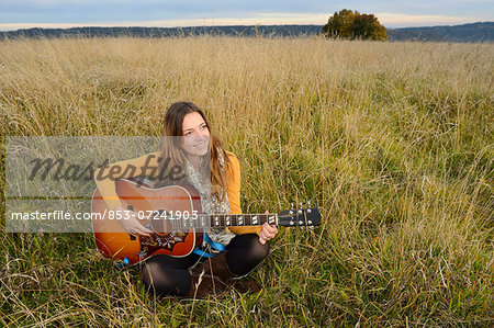 Smiling young woman playing guitar in field Stock Photo - Rights-Managed, Image code: 853-07241903