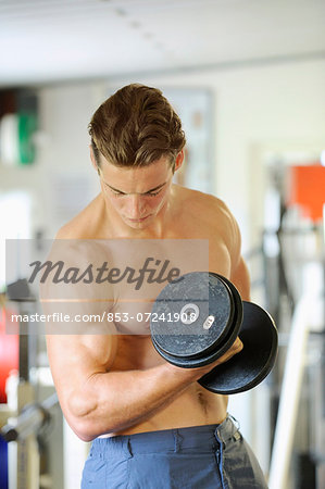 Young man exercising in fitness center Stock Photo - Rights-Managed, Image code: 853-07241908