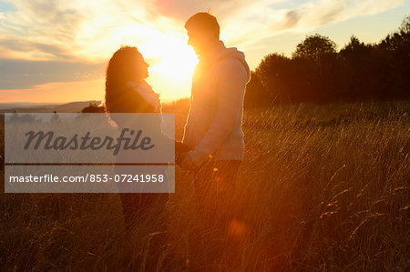 Couple at sunset on field Stock Photo - Rights-Managed, Image code: 853-07241958