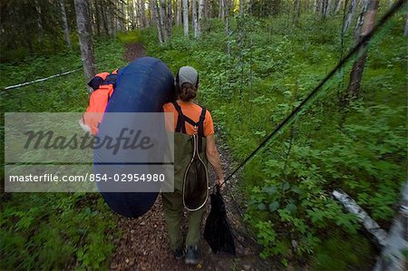 Fly fisherwoman hikes her float tube into Craig Lake to fish Rainbow Trout near the Alaska Highway & Tok Alaska southcentral summer Stock Photo - Rights-Managed, Image code: 854-02954980