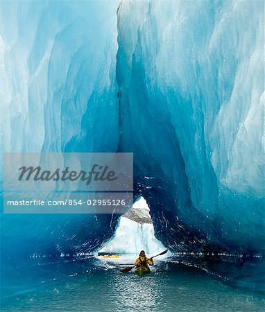 Sea Kayaker paddles through an ice cave amongst giant icebergs near Bear Glacier in Resurrection Bay near Seward, Alaska Stock Photo - Rights-Managed, Image code: 854-02955126