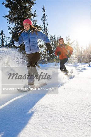 Two young women on snowshoes enjoy the outdoors near Homer, Alaska during winter. Stock Photo - Rights-Managed, Image code: 854-03537973