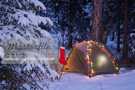 tent is set up in the woods with Christmas lights and stocking near ...