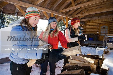Three young women collect and pile chopped wood near Homer, Alaska during winter. Stock Photo - Rights-Managed, Image code: 854-03539094