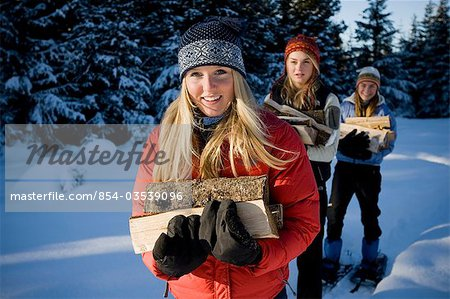 Three young women on snowshoes hauling chopped wood near Homer, Alaska during winter. Stock Photo - Rights-Managed, Image code: 854-03539096