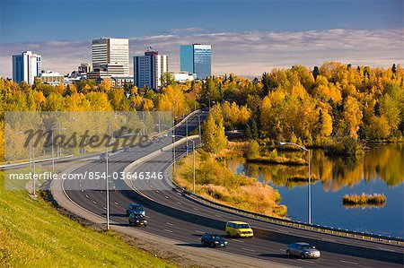 Scenic view of Minnesota Blvd. traffic along Westchester Lagoon on a sunny day with downtown Anchorage in the distance, Southcentral Alaska, Fall Stock Photo - Rights-Managed, Image code: 854-03646346