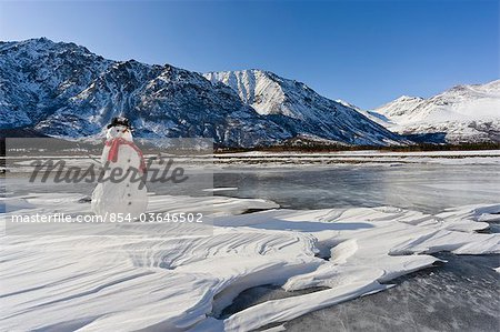 Snowman with a red scarf and black top hat sitting on the frozen Nenana River with the Alaska Range foothills in the background, Southcentral Alaska, Winter Stock Photo - Rights-Managed, Image code: 854-03646502
