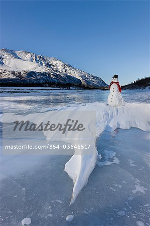 Snowman with a red scarf and black top hat sitting on the frozen Nenana River with the Alaska Range foothills in the background, Southcentral Alaska, Winter Stock Photo - Rights-Managed, Image code: 854-03646517