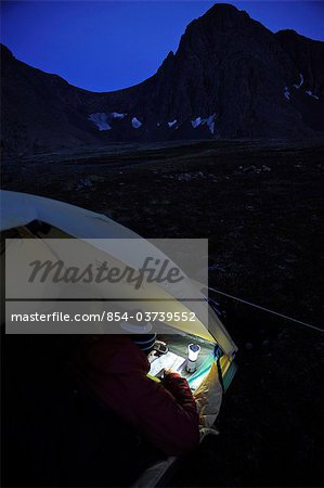 Woman in a tent at dusk consults a GPS and map while camping at Rabbit Lake, Chugach State Park, Southcentral Alaska, Autumn Stock Photo - Rights-Managed, Image code: 854-03739552