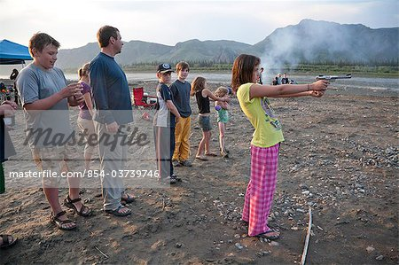 A 12 year old girl stands and shoots a .22 pistol in her pajamas and flip-flops at the edge of the Yukon River during a raft float trip, Yukon-Charley Rivers National Preserve  Interior Alaska, Summer Stock Photo - Rights-Managed, Image code: 854-03739746