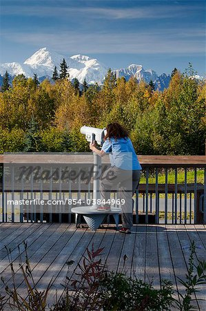 Woman visitor looks through telescope at the southside view of Mt. Mckinley and Alaska Range from the Alaska Veterans Memorial rest area along George Parks Highway, Denali State Park, Southcentral Alaska, Autumn Stock Photo - Rights-Managed, Image code: 854-03844969