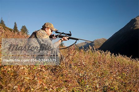 Male moose hunter sits on a hillside and aims with a rifle, Bird Creek drainage area, Chugach Mountains, Chugach National Forest, Southcentral Alaska, Autumn Stock Photo - Rights-Managed, Image code: 854-03845079