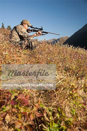 Male moose hunter sits on a hillside and aims with a rifle, Bird Creek drainage area, Chugach Mountains, Chugach National Forest, Southcentral Alaska, Autumn Stock Photo - Rights-Managed, Image code: 854-03845080