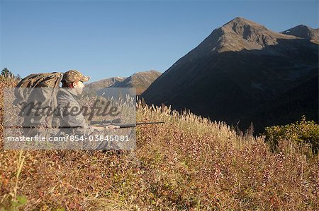Male moose hunter sits on a hillside and aims with a rifle, Bird Creek drainage area, Chugach Mountains, Chugach National Forest, Southcentral Alaska, Autumn Stock Photo - Rights-Managed, Image code: 854-03845081