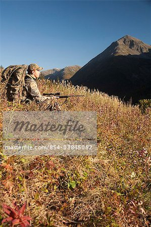 Male moose hunter sits on a hillside and aims with a rifle, Bird Creek drainage area, Chugach Mountains, Chugach National Forest, Southcentral Alaska, Autumn Stock Photo - Rights-Managed, Image code: 854-03845082