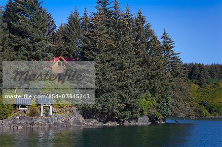 Scenic view of a log home powered by solar panels in Anton Larsen Bay, Kodiak Island, Southwest Alaska, Summer Stock Photo - Rights-Managed, Image code: 854-03845243