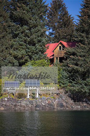 Scenic view of a log home powered by solar panels in Anton Larsen Bay, Kodiak Island, Southwest Alaska, Summer Stock Photo - Rights-Managed, Image code: 854-03845244