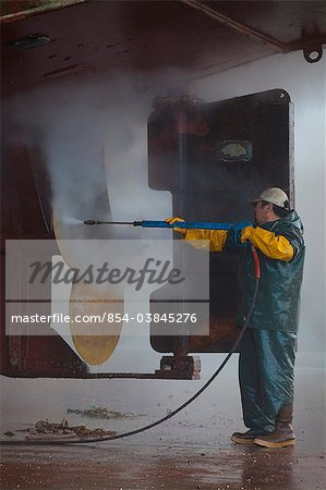 Crew member washing the propeller and stern of commercial fishing vessel using high-pressure hose and nozzle while boat rests on keel blocks and in Marine Travelift slings in Kodiak Boatyard, Kodiak, Kodiak Island, Southwest Alaska, Autumn Stock Photo - Rights-Managed, Image code: 854-03845276