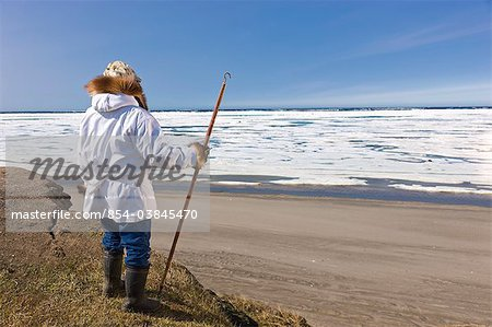 Portrait of a male Inupiaq Eskimo hunter wearing his Eskimo parka (Atigi) and seal skin hat and holding a walking stick at Old Utkeagvik original town site overlooking the Chukchi Sea, Barrow, Arctic Alaska, Summer Stock Photo - Rights-Managed, Image code: 854-03845470