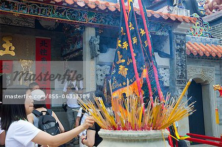 Worshipper offering incense at Pak Tai Temple during the Bun festival, Cheung Chau, Hong Kong Stock Photo - Rights-Managed, Image code: 855-06313309
