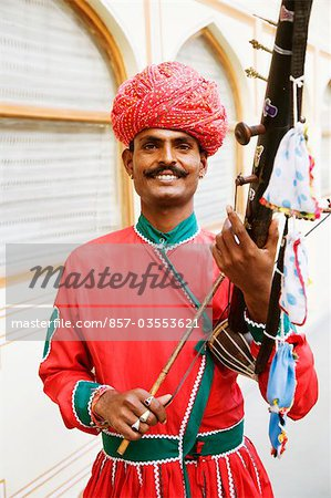 Mid adult man playing sarangi in a palace, City Palace, Jaipur, Rajasthan, India Stock Photo - Rights-Managed, Image code: 857-03553621