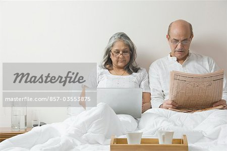 Man reading a newspaper with a woman using a laptop on the bed Stock Photo - Rights-Managed, Image code: 857-03553875