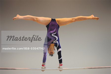 Gymnast performing on uneven parallel bars Stock Photo - Rights-Managed, Image code: 858-03047742