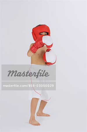 Kick boxer punching and looking at camera Stock Photo - Rights-Managed, Image code: 858-03050029