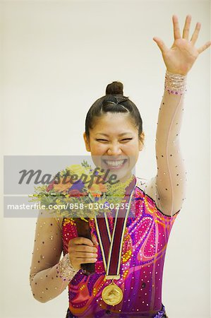 Gymnast wearing a medal and holding flower bouquet Stock Photo - Rights-Managed, Image code: 858-03050235