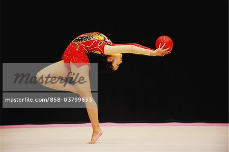 Gymnast bending backwards while performing with ball Stock Photo - Rights-Managed, Image code: 858-03799633
