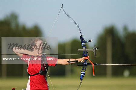 Young Female Archer Aiming at Target Stock Photo - Rights-Managed, Image code: 858-05604891