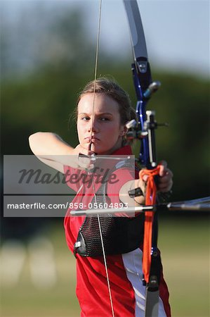 Young Female Archer Aiming at Target Stock Photo - Rights-Managed, Image code: 858-05604893