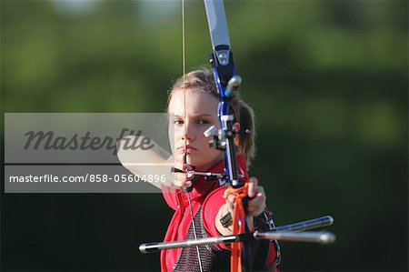 Young Female Archer Aiming at Target Stock Photo - Rights-Managed, Image code: 858-05604896
