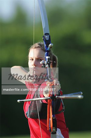 Young Female Archer Aiming at Target Stock Photo - Rights-Managed, Image code: 858-05604897