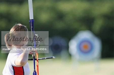 Young Female Archer Aiming at Target Stock Photo - Rights-Managed, Image code: 858-05604906