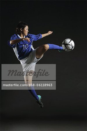 Japanese Woman Reaching Up To Hit Ball Stock Photo - Rights-Managed, Image code: 858-06118963