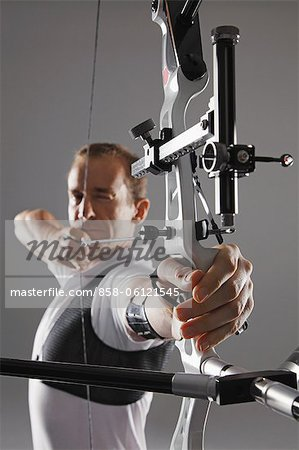 Male Archer Aiming With Bow And Arrow Stock Photo - Rights-Managed, Image code: 858-06121545