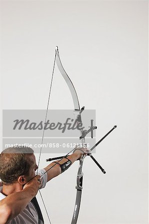 Man Aiming With Bow And Arrow Stock Photo - Rights-Managed, Image code: 858-06121556